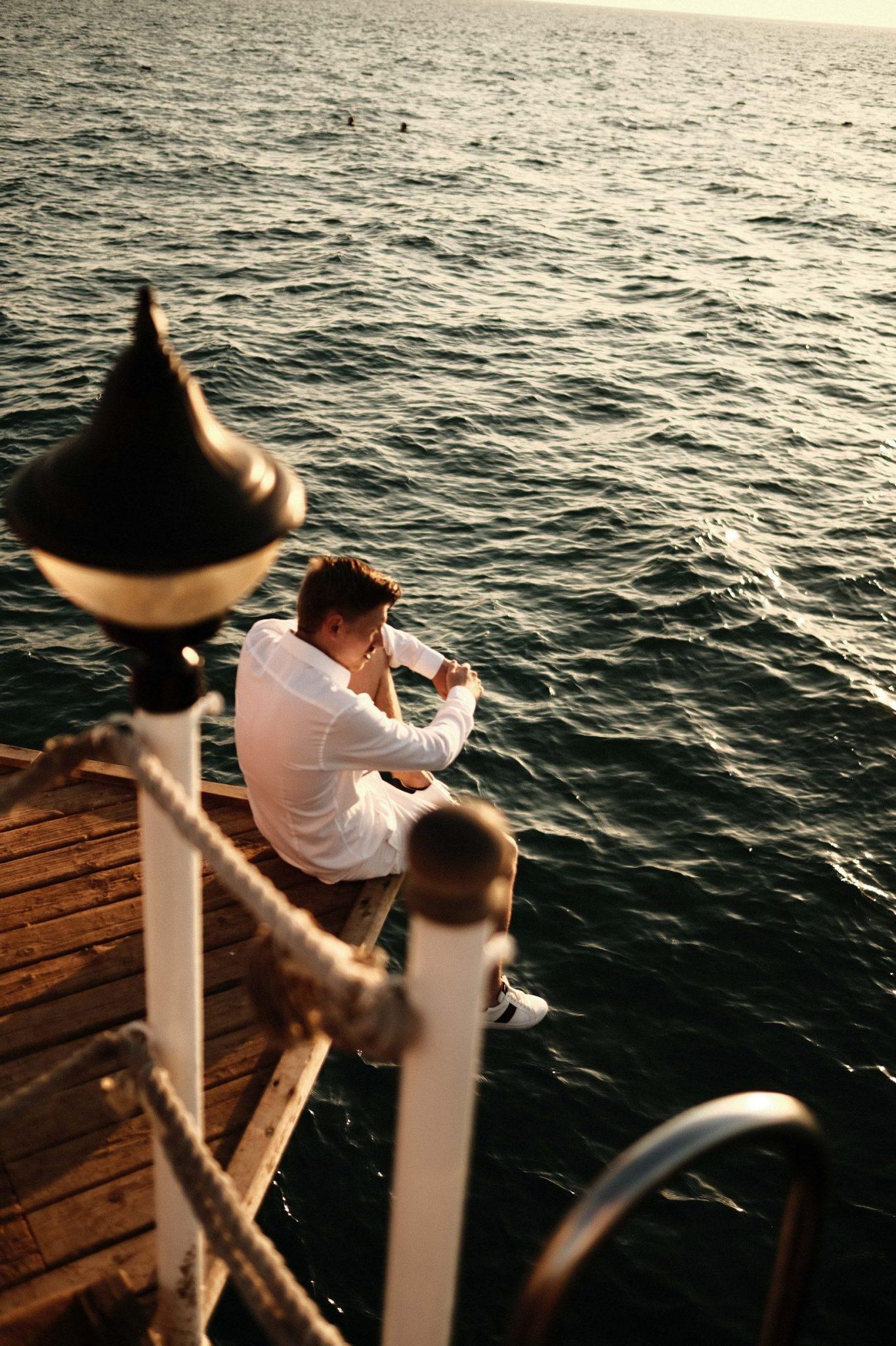 David Romanowski, sitzt auf einer kante hinter ihm das Meer.