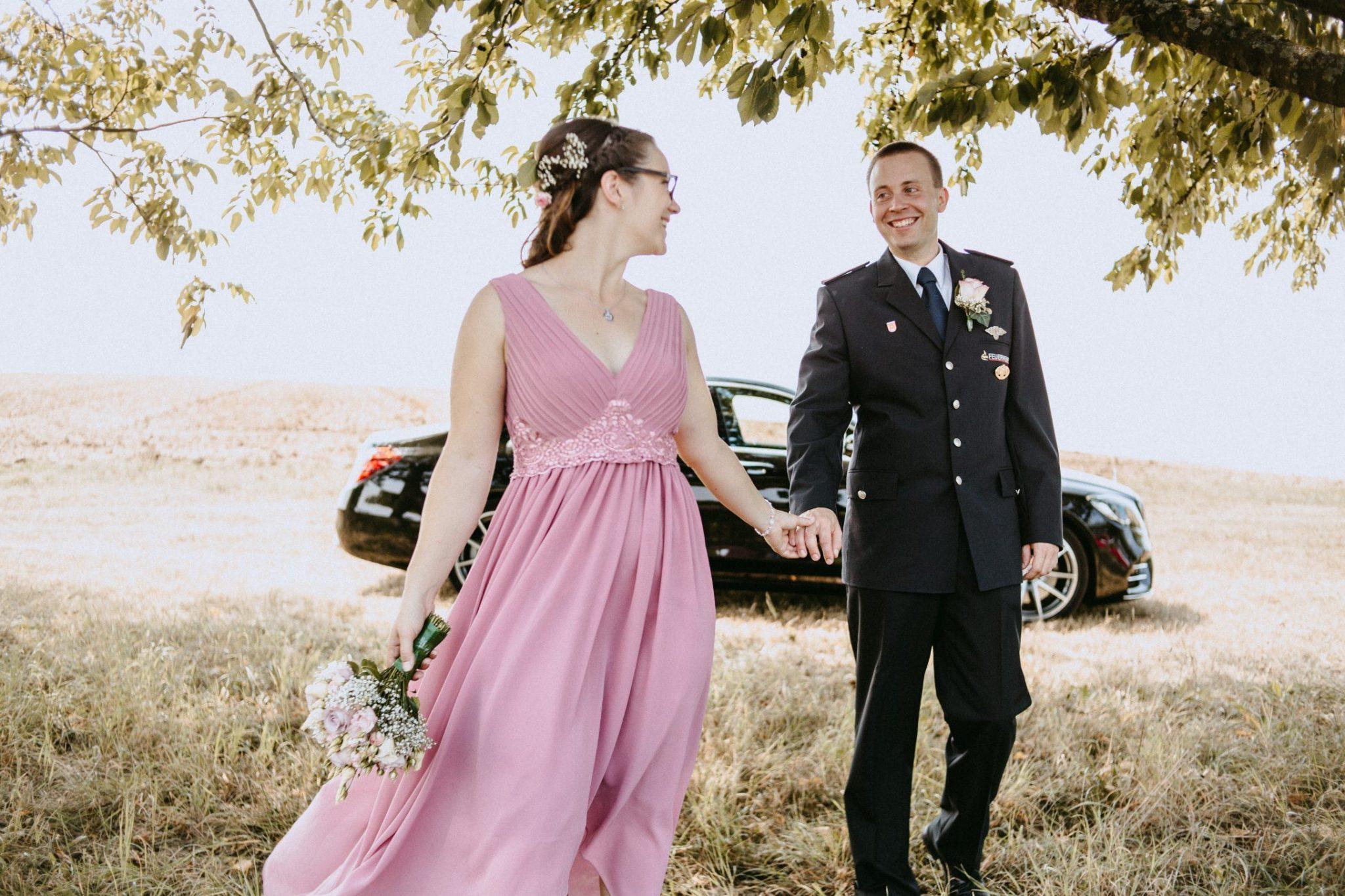 Rebekka und Alexander beim Brautpaarshooting, sie trägt ein wundervolles Rosa Kleid, im Hintergrund glänzt die Mercedes S-Klasse in schwarz