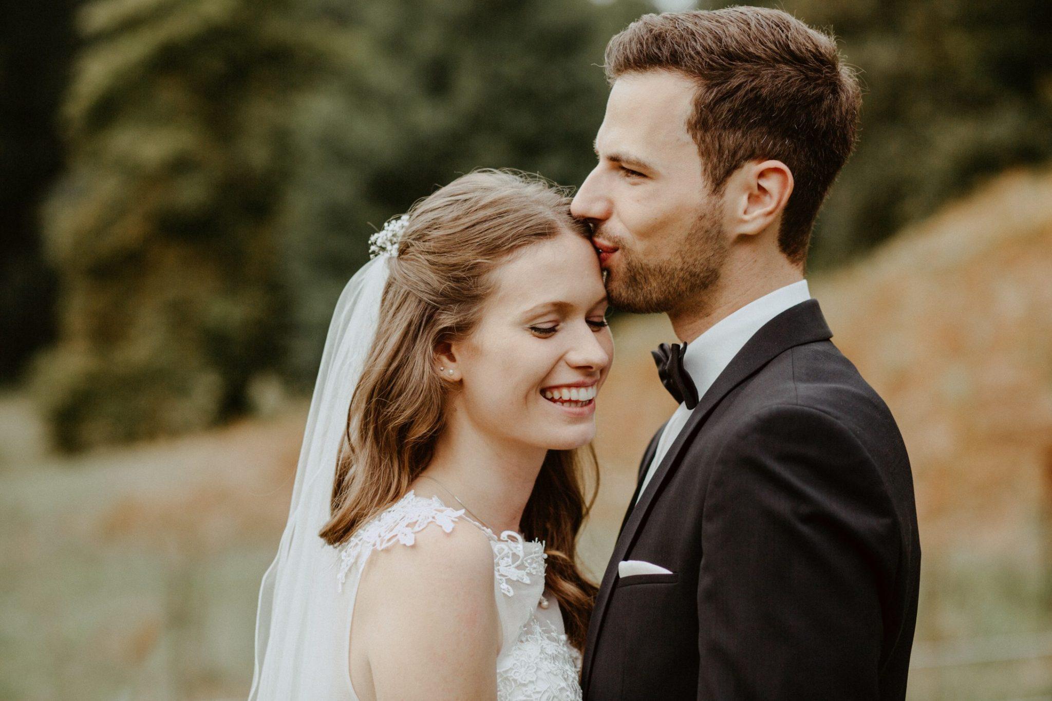 küssen des Paar auf einer Wiese (Brautpaarbild)